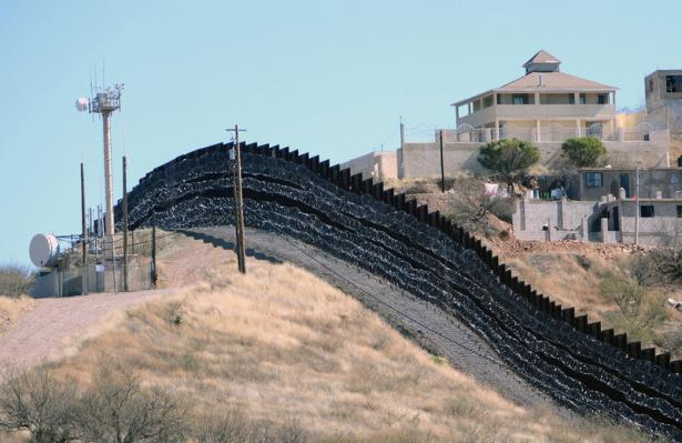intimidating border wall with barbed wire covering