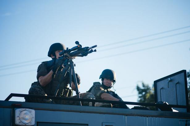A police sniper atop a Special Weapons and Tactical vehicle.