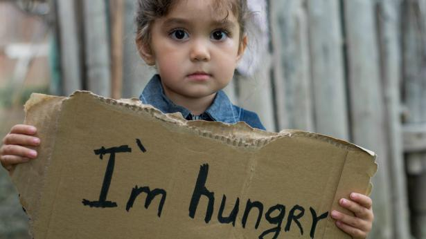 "A young child holds signs which says, ""I'm hungry."""