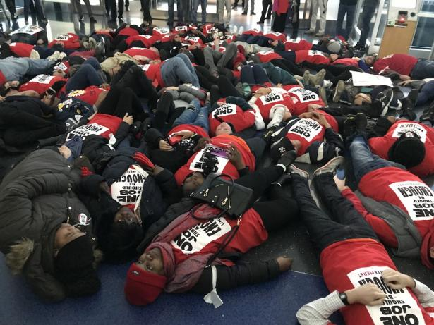"Hard-pressed workers stage ""die-in"" at JFK Airport."