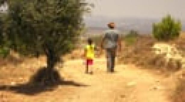 adult and child walking on a dirt path