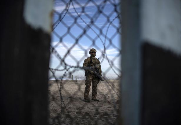 Armed US soldier standing at border with Mexico