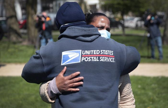 Annette Clay gets a hug from a postal worker during a ceremony honoring her daughter Unique Clay.