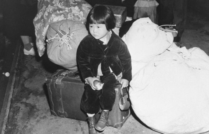 young Japanese-American girl sitting on bag waiting to go to concentration camp
