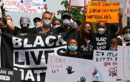 Workers at a rally with Black Lives Matter Signs