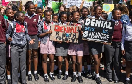 South African school children hold placards denouncing climate crisis denialism.