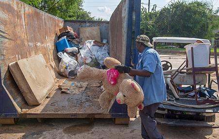 Workers throw away debris and ruined possessions from a public housing project in Texas.