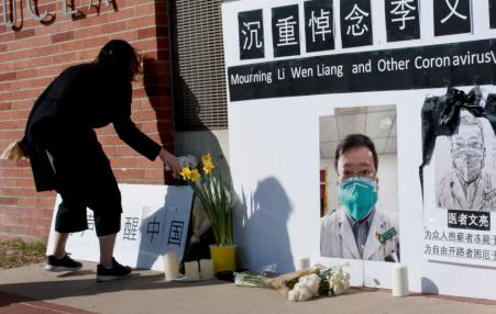 Women places a flower next to a photo of  Dr. Li Wenliang