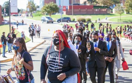students of color marching to vote at polls