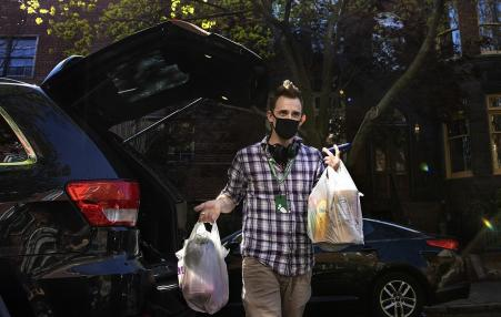 Man in a face mask holding bags of groceries