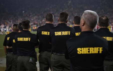 Sheriff's deputies on the sidelines of a National Football League game.