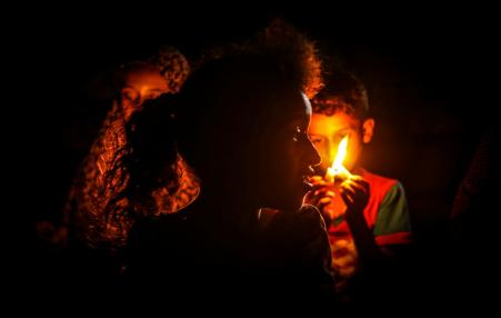Palestinian children sitting in the dark due to power outage