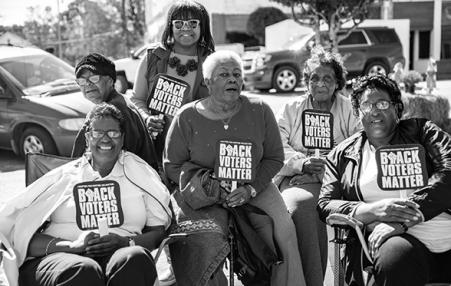 Black women with Black Voters Matter signs and fans