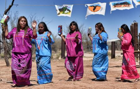 Indigenous people from the Tohono O'odham ethnic group dance and sing