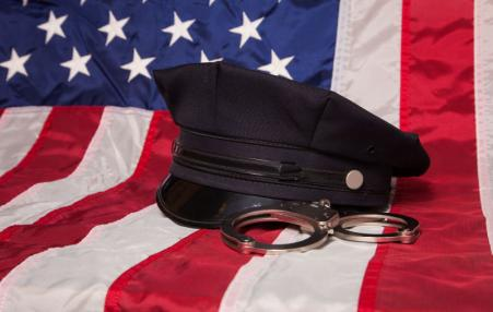USA flag with cop hat and handcuffs