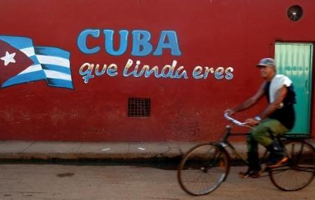 Cuban bicycle rider passing a mural