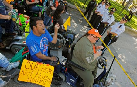 People in wheelchairs confronting police