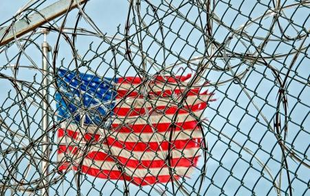 USA flag seen through barbed wire