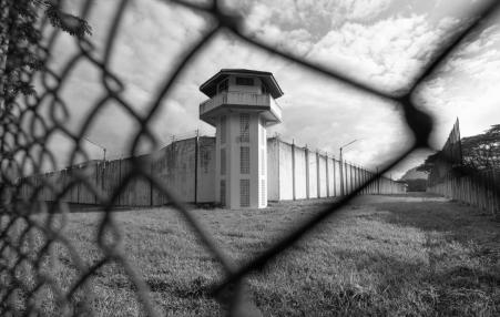 prison with guardtower and barbed wire fence