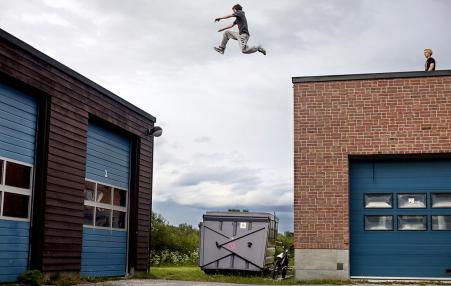 Teenagers leaps between buildings