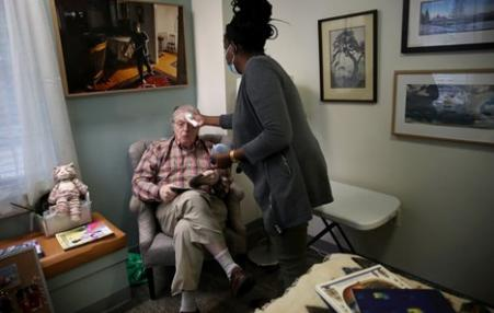 nursing aide helping older man