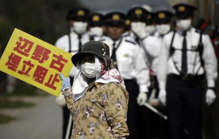 demonstrator in Okinawa surrounded by police