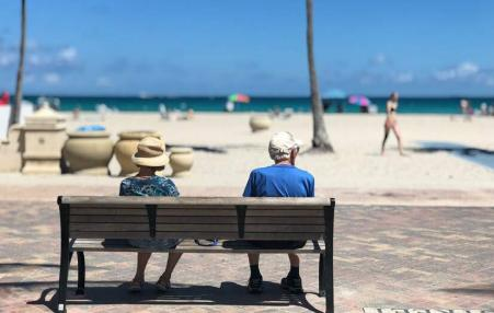 retirees sitting on a bench at the beach