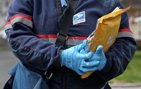 Postal worker holding a package wearing gloves.
